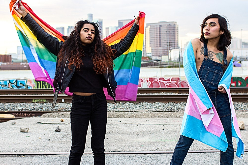 An image of two people, one with a rainbow flag and one with a trans flag in Los Angeles.