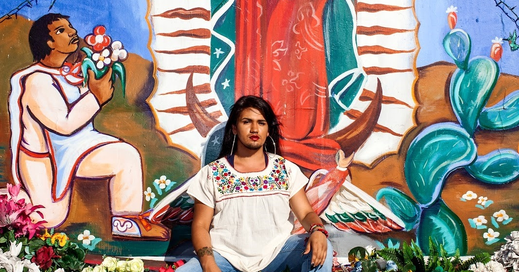 Image of Eve Moreno in front of a mural of the Virgen of Guadalupe. Un imagen de Eve Moreno frente a un mural de la Virgen de Guadalupe