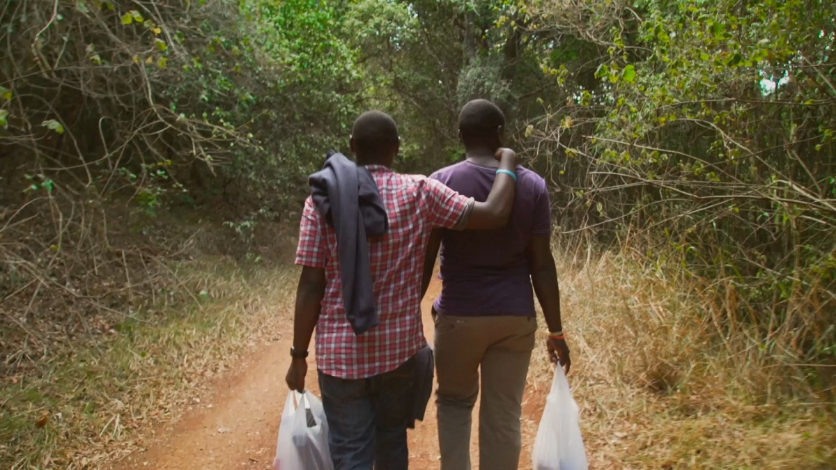 Two black men in casual clothes walk through a light forest path together. They are both carrying plastic bags with goods inside. The man on the left has his arm on the shoulder of the other man.