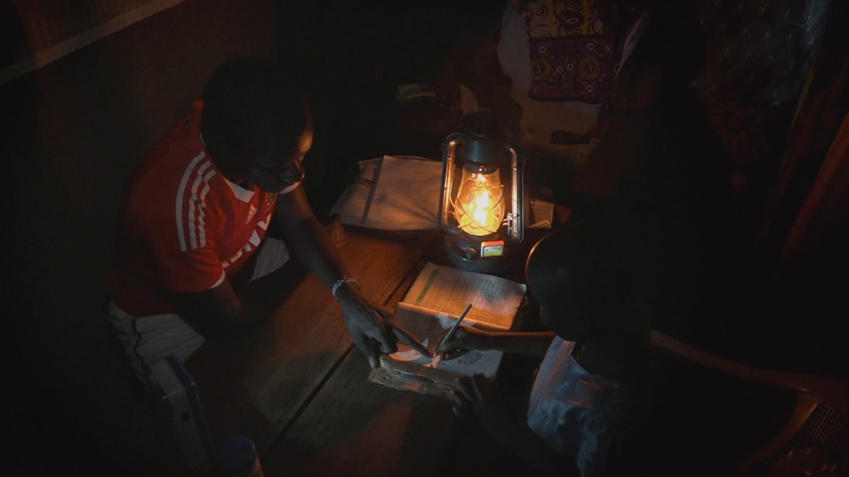 An African father is tutoring his daughter in a small, dimly lit room. A portable electric lamp set on the table is the only light source.