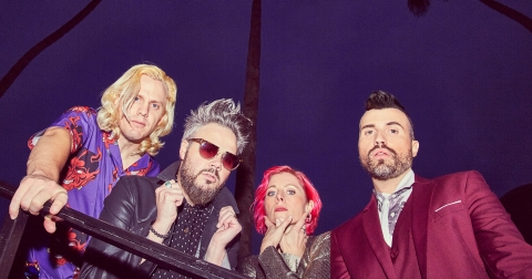 the members of Neon Trees in bright casual clothing against a dark purple background looking down at the camera
