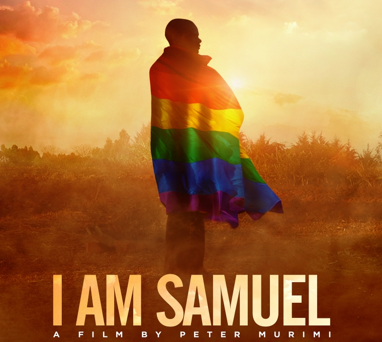 A young black man faces away from the camera while wearing a rainbow flag draped around his shoulders. He is standing in the middle of the Kenyan countryside.