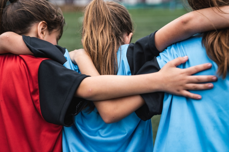 three girls in soccer uniforms have their arms on each others shoulders