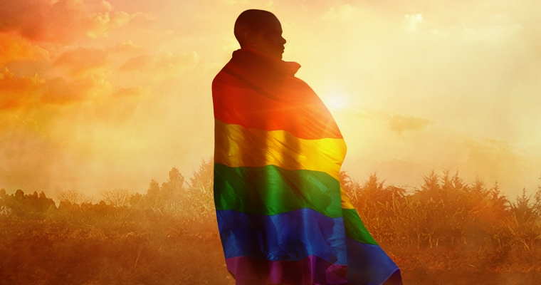 A young black man facing away from the camera while wearing a rainbow flag draped around his shoulders.
